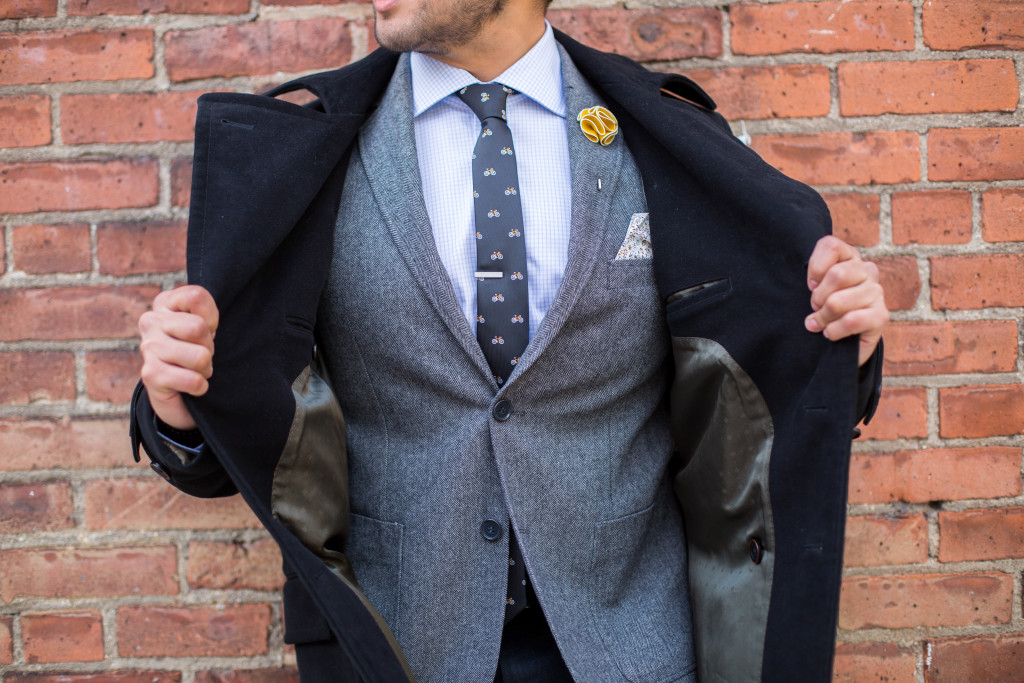 grey suit with bicycle tie and black top coat